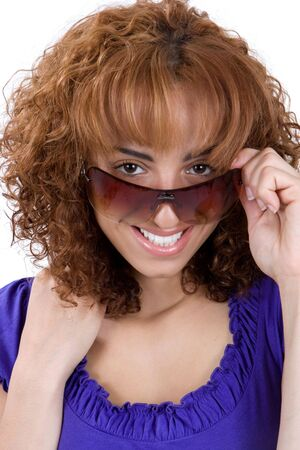 A young business woman with auburn hair peeks over her sunglasses and smiles. Stock Photo - 4674139