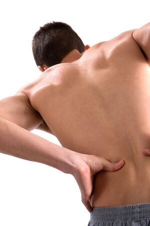 back ache: A young man bends over with an aching back rubbing it in pain. Stock Photo