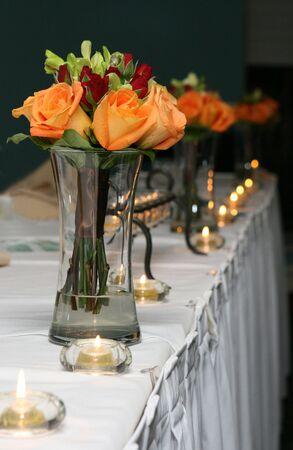 bridesmaids: Bridesmaids bouquets sit in vases of water on the head table at a wedding reception. Stock Photo