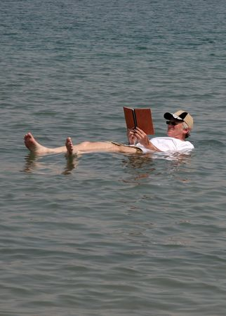 A senior adult reads a book while floating on the Dead Sea in Israel. The high salt content in the water allows a person to float high in the water with no effort. Stock Photo