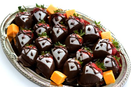 lookalike:  A platter of strawberries are decorated in dark and white chocolate to look like they are dressed in tuxedos.