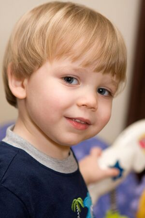 A mischievous toddler gives a questioning look.