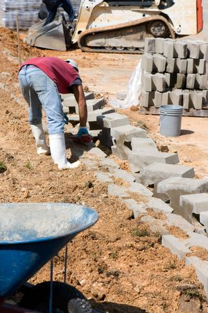 wage earner: A construction worker lays concrete blocks for a retaining wall.