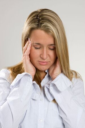 throbbing: A young woman holds her head in pain. Stock Photo