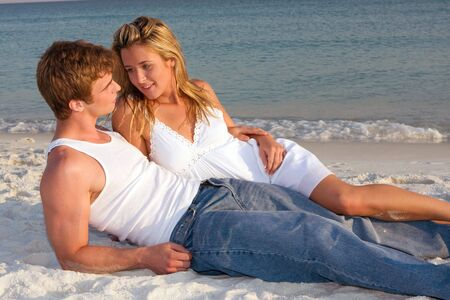A young adult couple lay on the beach talking. Stock Photo - 5047107