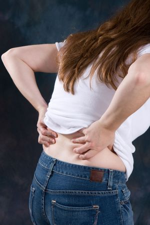 back rub: A woman bends over rubbing the ache in her back. Stock Photo