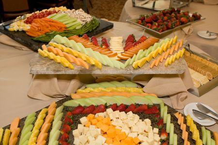 결혼식 피로연을 위해 과일, 치즈, 채소 및 크래커 등의 쟁반이 뷔페 테이블에 전시됩니다.