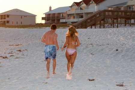 A young couple run on the sandy beach toward the house in the late afternoon light. Stock Photo