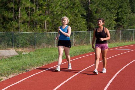 Dos alumnas jóvenes ejercicio por el poder caminar en la pista de la universidad.