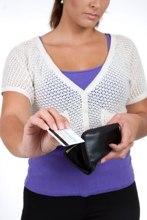 retrieves: A woman retrieves a credit card from her purse to make a purchase. Stock Photo