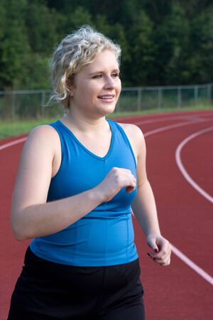 sweaty: A young woman who is somewhat overweight runs the track to burn calories. Stock Photo