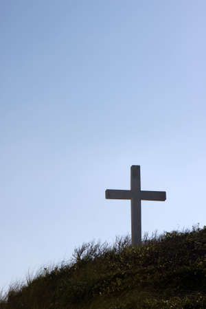 forgiven: Silhouette of a cross on a hill with a clear blue sky background located on Pensacola Beach, Florida. Can be used for many applications with text. Stock Photo