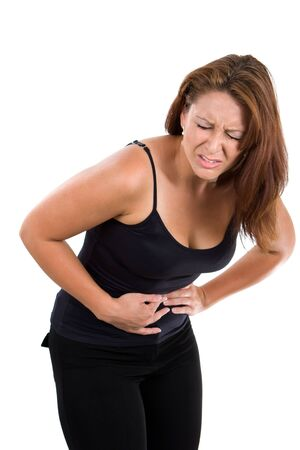 Woman holds her stomach and bends over in pain from abdominal cramps. photo