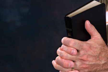 Mature mans hands holds bible in praying position with dark blue background. Room for copy on left.
