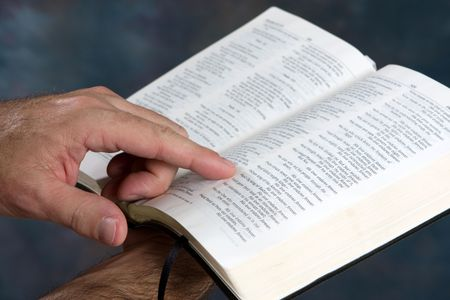 bible reading: Man holds open bible and reads from scripture.