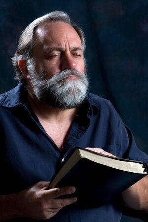 Bearded man praying while holding Holy Bible.
