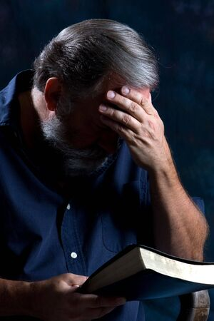 gospels: Man holds his head in one hand and bows to pray while holding his bible in the other. Stock Photo