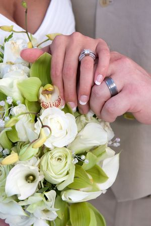 Bride and grooms hand over flower showing the wedding rings. Stock Photo