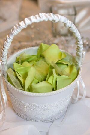 flowergirl: White flower girls basket contains green fabric flower petals.