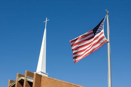 United States flag flies in front of a church steeple topped by a Christian cross. photo