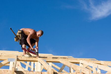 rafters: Carpenter uses a pneumatic nail gun to attach rafters and braces to a roof system on a new home under construction.