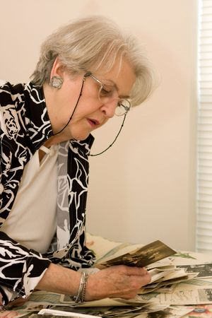 old photo: Senior adult looks at old vintage photographs and reminisces about the past.
