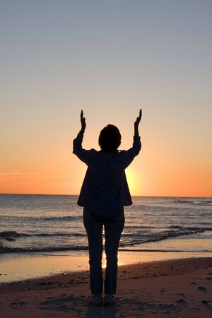 worshipper: Woman raises her hands toward heaven in praise and worship. Room for copy at top. Stock Photo
