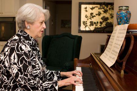 アクティブな退職後の生活で年配の大人女性は彼女の家でピアノを弾きます。