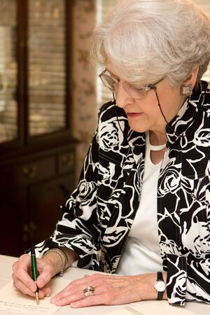 Senior woman writing personal letter to a friend in her home. Stock Photo - 5874493