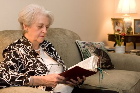 gospels: Senior adult sits on the couch in her home and studies the bible. Old photos on table in background are of her as a young woman. Stock Photo
