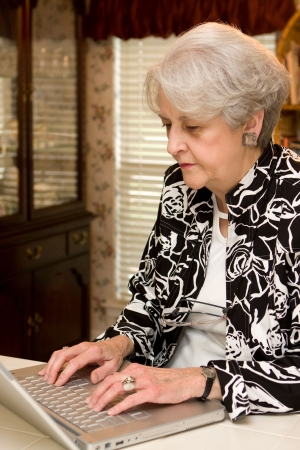Senior adult woman working at home on a laptop computer trying to make extra income.