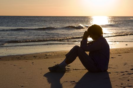 Mature woman sits on the beach with her head bowed and praying as the sun sets on the water.