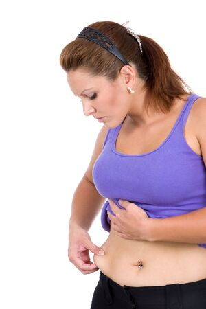 Woman looks at the excess flesh around her waist as she gives it a pinch.