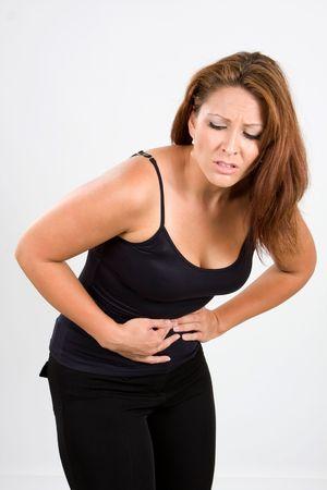 굽힘: Woman bends over in pain for stomach cramps.