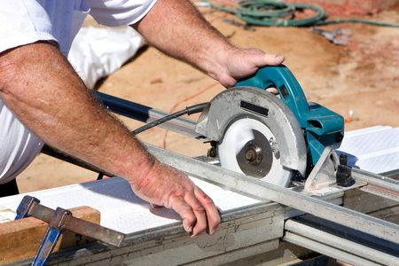 Construction worker uses a electric powered circular saw to cut soffit for a home being built. Stock Photo - 6239992
