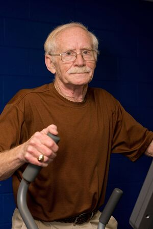 Happy senior man works out on an elliptical machine at the gym. photo
