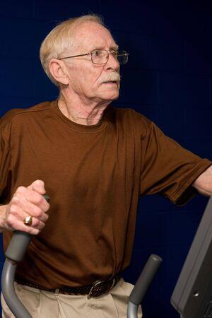 eliptica: Senior hombre trabajando en una m�quina el�ptica. Foto de archivo