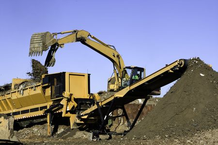 Frontend loader dumps landfill into a screener to separate solid waste from good soil which is transported by conveyor belt to preserve landfill space. Stock Photo - 6301319