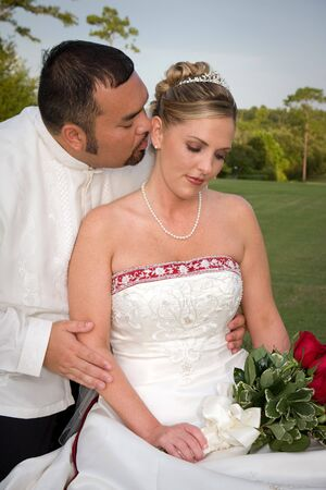 Romantic bride and groom share a tender embrace on the grass during a break at the reception. Reklamní fotografie