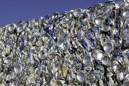 Crushed aluminum beverage cans stacked for recycling against a blue sky. Stockfoto