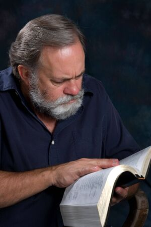 Mature minister with gray beard studies his bible.