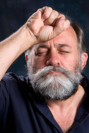 grieved: Look of disappointment on a mans face with his fist clenched on the forehead. Stock Photo