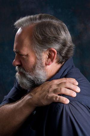 spinal adjustment: Man massages his painful shoulder. Stock Photo