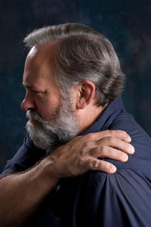 Man massages his painful shoulder. Stockfoto