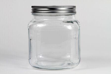 Empty clear glass jar with screw lid.