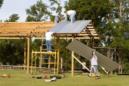 Four construction workers apply corrugated metal sheets to the rafters of a pole barn by fastening with screw-guns. Standard-Bild