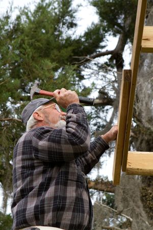 rafter: Senior adult uses a hammer to drive nails into a wood roof rafter.
