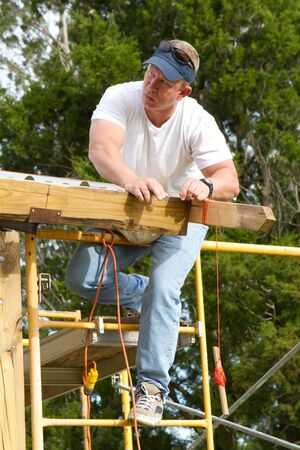 rafters: Carpenter checks the straight line before fastening metal roofing to the rafters of a barn.