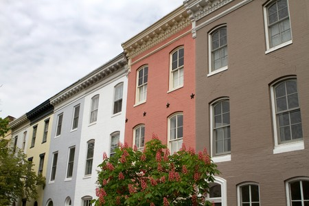 rij huizen: Multicolored row houses with a decorative soffit against a cloudy sky in Baltimore, Maryland.