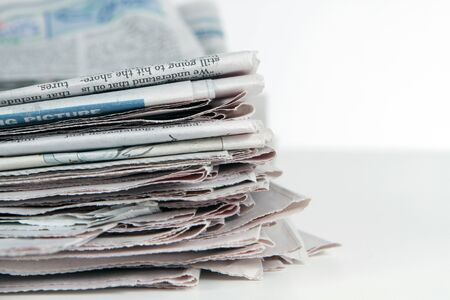 Stack of newspapers sit on a white background. photo